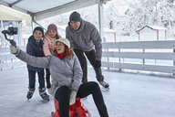 Family with two kids on the ice rink, taking selfies with their smartphone - ZEDF01856