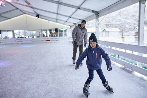 Father and son ice skatng together, having fun on the ice rink - ZEDF01871