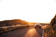 Spain, classic car driving on road during sunset - ACPF00394