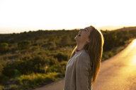 Laughing young woman on country road at sunset - ACPF00397