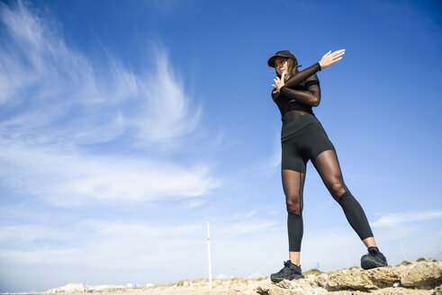Sportive woman standing on stone wall doing strecthing exercise - JSMF00743