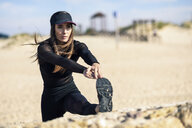 Sportive woman stretching her leg on stone wall - JSMF00749