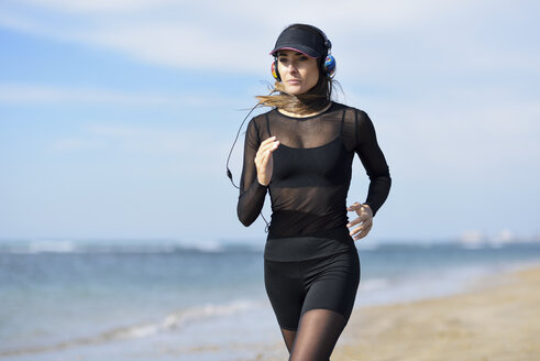 Sportive woman running on the beach - JSMF00752