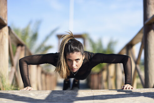 Spain, Andalusia, Cadiz. Middle-aged woman with fit body doing push-ups on a wooden bridge on the beach. Sports and fitness concept. - JSMF00755