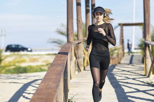 Sportive woman running on wooden bridge - JSMF00758