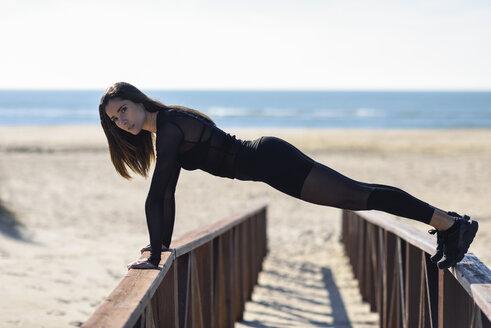 Sportive woman doing push-ups on railing of a wooden bridge - JSMF00764