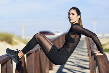 Sportive woman exercising on railing of a wooden bridge - JSMF00767