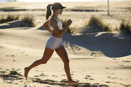 Sportive woman running along sand dunes on the beach - JSMF00770