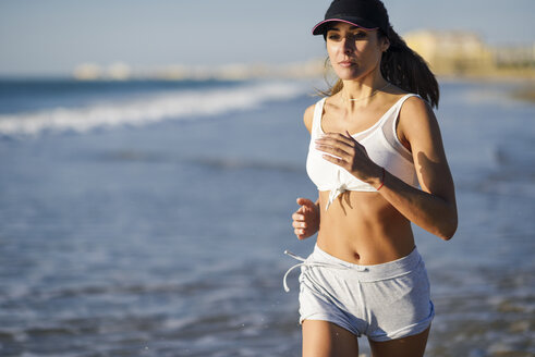 Sportive woman running on the beach - JSMF00773