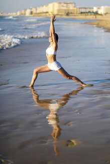 Sportive woman doing yoga on the beach - JSMF00776