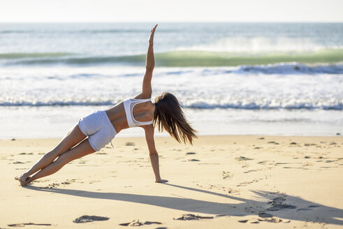 Spain, Andalusia, Cadiz. Middle-aged woman with fit body, doing abdominal exercises on the beach sand. Sports and fitness concept. - JSMF00785