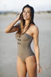 Portrait of smiling beautiful woman wearing swimsuit on the beach - JSMF00788