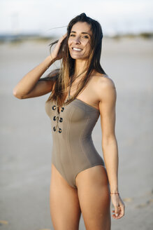 Spain, Andalusia, Cadiz. Middle-aged woman with fit body wearing a beautiful swimsuit on a beautiful sandy beach. Lifestyle and summer concept. - JSMF00788