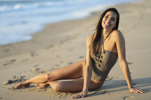 Portrait of smiling beautiful woman wearing swimsuit sitting on the beach - JSMF00791