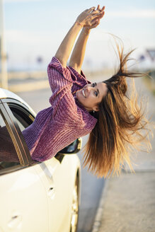 Portrait of happy woman leaning out of car window - JSMF00794