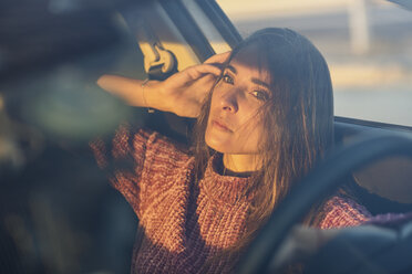 Portrait of serious woman sitting in car at sunset - JSMF00797