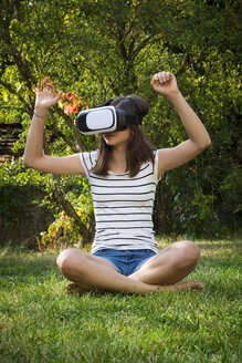 Girl sitting on meadow in the garden using Virtual Reality Glasses - LVF07715