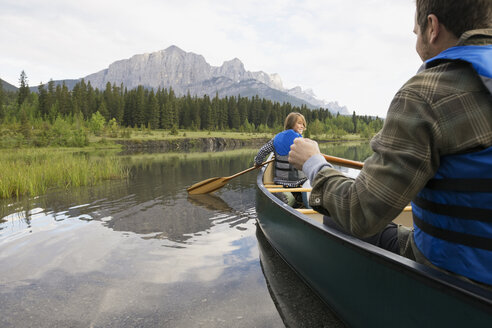 Father and son rowing canoe in still lake - HEROF08211