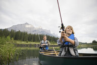 Father and son fishing in canoe in lake - HEROF08214