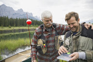 Father and son examining fishing tackle - HEROF08232