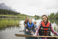 Family sitting in canoe in still lake - HEROF08244