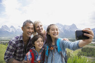 Family taking cell phone picture on rural hillside - HEROF08259