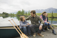 Family sitting by canoe by still lake - HEROF08265