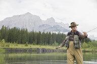 Older man fishing in still lake - HEROF08274