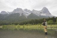Older man fishing in still lake - HEROF08277
