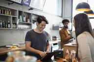 Cafe cashier using digital tablet at counter - HEROF08403