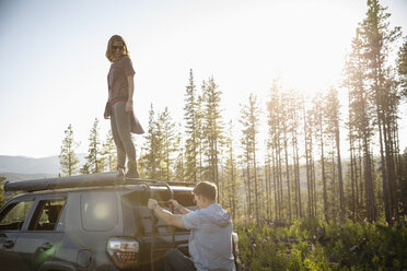 Couple enjoying overland adventure, standing at SUV in sunny remote forest, Alberta, Canada - HEROF08454