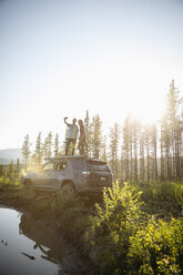 Couple enjoying overland adventure, taking selfie on top of SUV in sunny remote forest, Alberta, Canada - HEROF08457