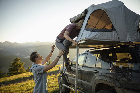 Couple climbing into SUV rooftop tent in idyllic mountain field, Alberta, Canada - HEROF08460
