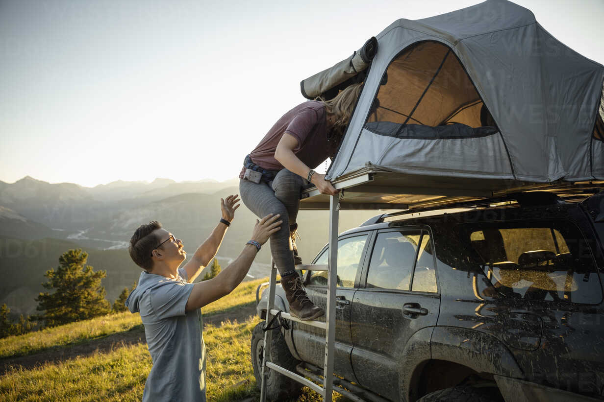 Couple climbing into SUV rooftop tent in idyllic mountain field, Alberta, Canada - HEROF08460 - Hero Images/Westend61