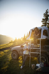 Couple camping, relaxing at SUV rooftop tent in sunny, idyllic field, Alberta, Canada - HEROF08463