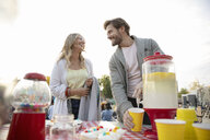 Couple pouring lemonade at movie in the park - HEROF08514