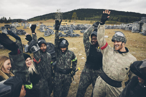 Enthusiastic friends paintballing, cheering in field - HEROF08532