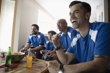 Enthusiastic Latinx multi-generation family playing sports video game - HEROF08559