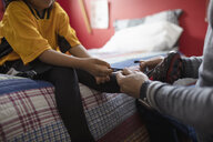 Father tying soccer shoes for son on bed - HEROF08562