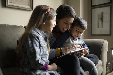Latinx mother and children using digital tablet on sofa - HEROF08652