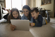 Latinx family using digital tablet on living room floor - HEROF08655