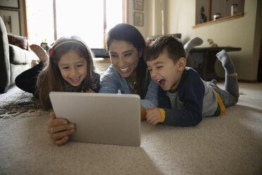 Latinx family using digital tablet on living room floor - HEROF08655