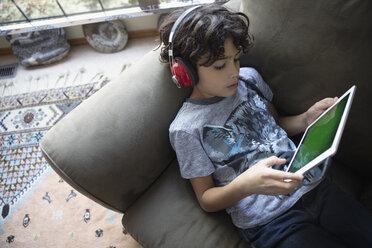 Latinx boy with headphones using digital tablet on sofa - HEROF08670