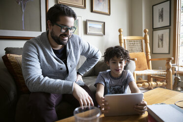 Latinx father and son using digital tablet in living room - HEROF08673