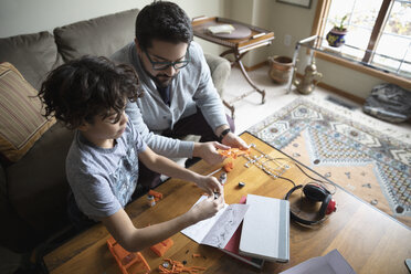 Latinx father and son assembling model car - HEROF08676