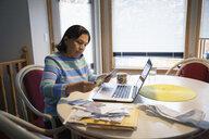 Latinx senior woman paying bills at laptop - HEROF08682