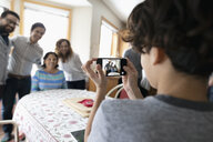 Latinx boy with camera phone photographing family - HEROF08685