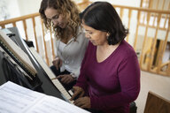 Latinx daughter and senior mother playing piano - HEROF08688