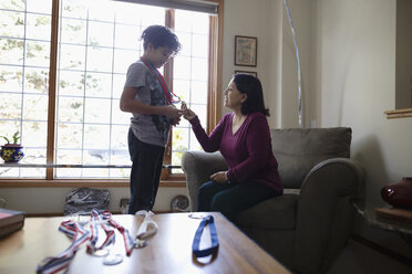 Latinx grandson showing sports medals to grandmother - HEROF08691