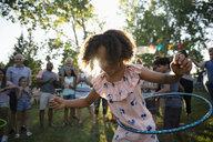 Playful girl spinning in plastic hoop at summer neighborhood block party in park - HEROF08718